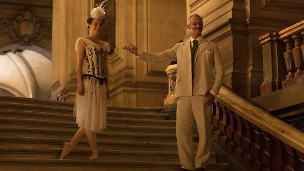 Der berühmte Choreograf Menkin (Javone Prince, r.) stellt im Jahr 1905 seine neue Primaballerina der Öffentlichkeit vor. Es ist Thea (Hannah Dodd, l.), die alle mit ihrer Tanzkunst beeindruckt. | Rechte: ZDF/Cottonwood Media/Nicolas Velter