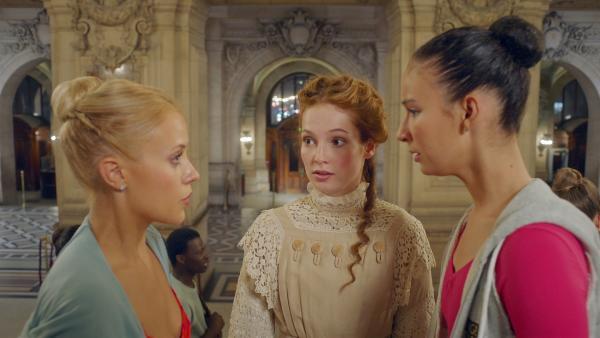 Thea (Hannah Dodd, M.) ist zurück in der Gegenwart. Allerdings unfreiwillig. Auch Lena (Jessica Lord, l.) und Ines (Eubha Akilade, r.) sind erstaunt über ihr plötzliches Auftauchen. | Rechte: ZDF/Cottonwood Media/Nicolas Velter