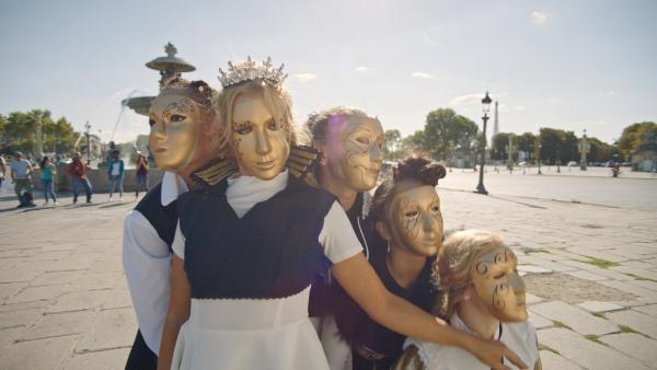 Lena (Jessica Lord, Mi.) und ihre Tanzgruppe bei einem Überraschungsauftritt mitten in Paris. Um unerkannt zu bleiben tragen alle goldene Masken vor dem Gesicht. | Rechte: ZDF/2019 - Cottonwood Media/Opéra national de Paris
