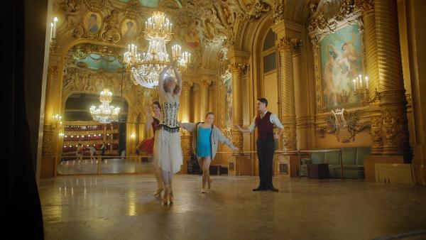 Romy (Isabelle Allen, Mi.) probt mit der berühmten Tänzerin Anna Pavlova (Justine Foiret), die sie mit Hilfe von Lenas Zeitmesser zu sich in die Gegenwart geholt hat, Tanzschritte ein. Doch damit hat sie unwissentlich einen Alarm in der Zeitreisenbehörde ausgelöst. | Rechte: ZDF/2020 Cottonwood Media/Opéra national de Paris/ZDF Enterprises