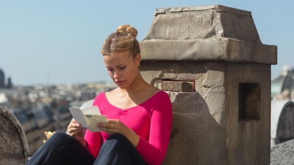 Lena (Jessica Lord) sitzt an ihrem Lieblingsplatz auf dem Dach der Oper in Paris und liest den Abschiedsbrief von Max, der die Ballettschule überraschend verlassen hat. Sie versteht nicht, wieso er sich nicht persönlich von ihr verabschiedet hat. | Rechte: ZDF/Nicolas Velter