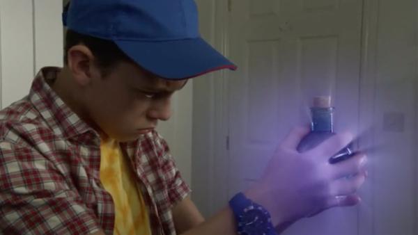 Ifan greift nach einer magischen Flasche. | Rechte: S4C