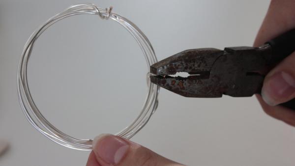 Forme mit einer Zange den Draht zu einem Armreif und umwickle die Enden, damit der Draht seine Form nicht verliert. | Rechte: KiKA