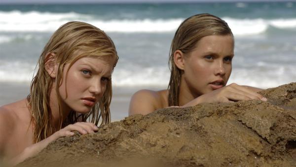 Rikki (Cariba Heine, li.) und Emma (Claire Holt, re.) haben sich hinter einem Felsen versteckt. Sie wollen ihr Meerjungfrauen-Geheimnis bewahren.   Rechte: ZDF/Jasin Boland
