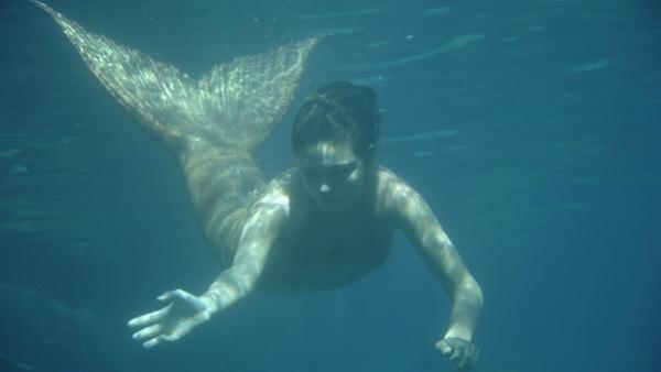Cleo (Phoebe Tonkin) schwimmt als Meerjungfrau im offenen Meer. Sie ist auf der Suche nach dem Fischer, der illegal die Schildkröten fängt. | Rechte: ZDF/Jasin Boland