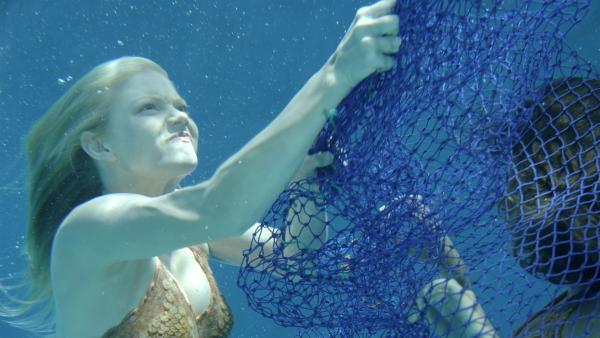 Cleo (Phoebe Tonkin, im Netz) hat sich bei ihrer Suche nach dem illegalen Schildkröten-Fischer in einem Fischernetz verfangen. Sie wird von Rikki (Cariba Heine, li.) befreit. | Rechte: ZDF/Jasin Boland