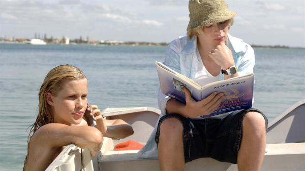 Lewis (Angus McLaren, li.) studiert ein Buch mit mystischen Seewesen, während Emma (Claire Holt) als Meerjungfrau im Meer unterwegs ist. | Rechte: ZDF/Jasin Boland