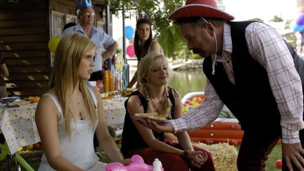 Cleos Dad (Alan David Lee) hat eine Geburtstagsparty für Cleo organisiert. Er scheint nur leider vergessen zu haben, dass seine Tochter nicht sechs sondern sechzehn wird.  Verkleidet im Cowboykostüm versucht er zumindest Emma (links, Claire Holt) und Rikki (Mitte, Cariba Heine) zu begeistern. | Rechte: ZDF/Jasin Boland