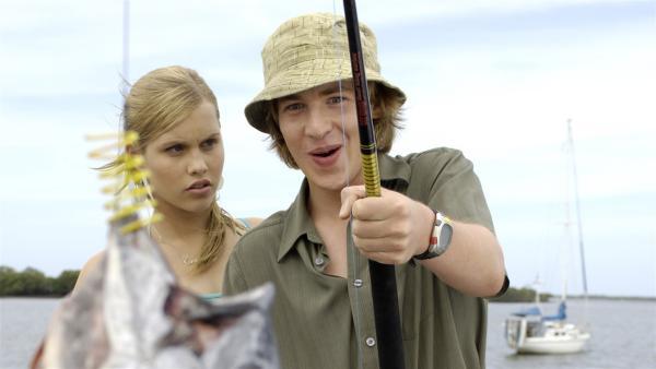 Wow – Lewis (Angus McLaren) hat einen Riesenfisch an der Angel. Emma (Claire Holt) ahnt wer dahintersteckt. | Rechte: ZDF/Jasin Boland