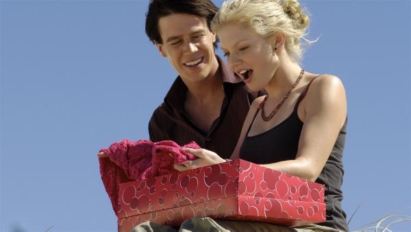 Zane (Burgess Abernethy, li.) schenkt Rikki (Cariba Heine) das rote Kleid, das ihr so gut gefallen hat.   Rechte: ZDF/Jasin Boland