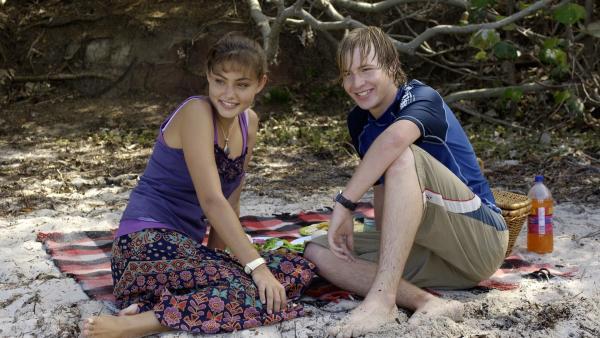 Cleo (Phoebe Tonkin, li.) hat für Lewis (Angus McLaren, re.) ein romantisches Dinner auf Mako Island organisiert. | Rechte: ZDF/Jasin Boland