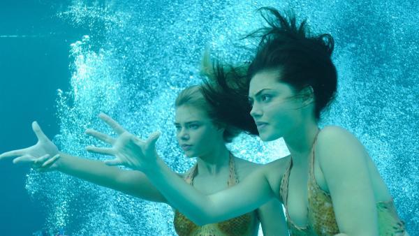 Cleo (Phoebe Tonkin, re.) und eine noch unbekannte Meerjungfrau (Indiana Evans, li.) kämpfen gegen das Böse an.   Rechte: ZDF/Jasin Boland