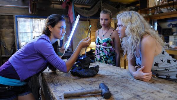 Cleo (Pheobe Tonkin, li.), Rikki (Cariba Heine, re.) und Bella (Indiana Evans) untersuchen einen Gesteinsbrocken aus der Höhle auf Mako Island und entdecken einen geheimnisvollen Kristall.   Rechte: ZDF/Jasin Boland