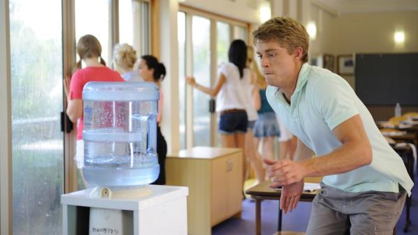 Im Klassenraum spielt das Wasser verrückt. Will (Luke Mitchell) versucht den Wasserbehälter festzuhalten, um Rikki, Cleo und Bella vor Spritzwasser zu schützen. | Rechte: ZDF/Jasin Boland