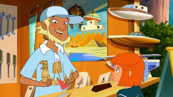 Der Verkäufer zeigt Lilli ein Schilfbootmodell der Uros.   Rechte: WDR