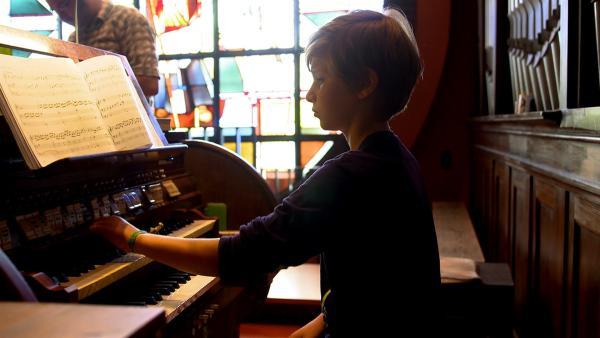 Felix spielt Orgel in der Kirche. | Rechte: MDR/Cine Impuls