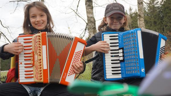Leonie und Kimik tauschen für einige Wochen ihr Hobby. Leonie zeigt Kimik aber noch, wie das Akkordeon funktioniert. | Rechte: MDR/Martin Reißmann