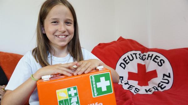 Lina präsentiert stolz ihren Erste-Hilfe-Koffer | Rechte: MDR/Martin Reißmann