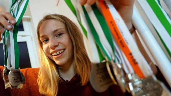 Die 14-Jährige Hanna ist Synchronschwimmenrin und zeig ihre Medaillen. | Rechte: MDR/Cine Impuls