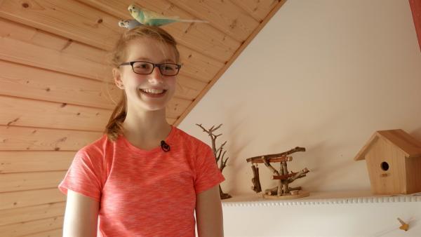 Adele ist 13 Jahre alt und liebt das Klettern. Hier posiert sie mit ihren Vögeln vor der Kamera. | Rechte: MDR/Cine Impuls