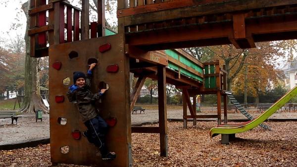 Jakob liebt es zu Klettern. Doch auf dem Spielplatz sind die Klettersteige nicht sehr hoch und es regnet noch dazu. | Rechte: ZDF/Studio.TV.Film GmbH