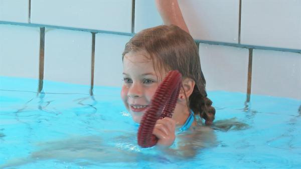Marietta muss auch vom Beckenrand ins Wasser springen und in schultertiefem Wasser nach einem Ring tauchen. | Rechte: KiKA
