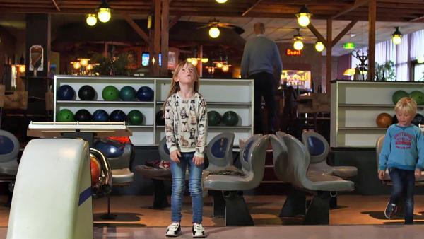 Lola ist mit ihrem Zwillingsbruder Flint in einer Bowlinghalle. Gespannt schaut Lola auf die Anzeigentafel. Hat sie das Spiel gewonnen? | Rechte: ZDF/KRO-NCRV