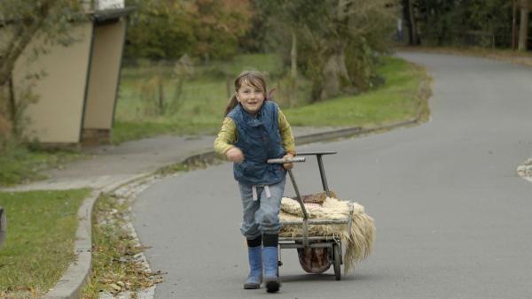Alice fährt mit ihrem Bollerwagen und den gesammelten Sachen zum Gartenhäuschen. | Rechte: KiKA