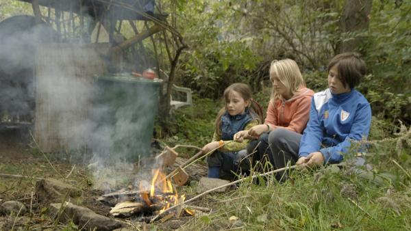 Nach getaner Arbeit machen Alice (li.), ihre Schwester (re.) und deren Freundin (Mi.) noch ein schönes Lagerfeuer. | Rechte: KiKA