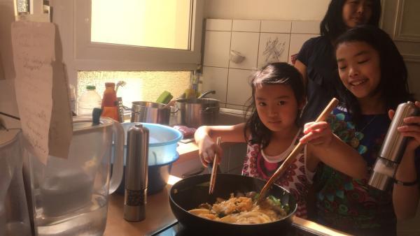 May-Lin (li.) rührt in der Pfanne die leckeren Nudeln. Das ist gar nicht so einfach. Ihre zehnjährige Schwester Yuc-Lin (re.) hilft ihr dabei. | Rechte: ZDF/Studio.TV.Film