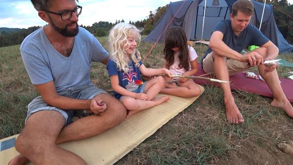 Lia und Lola mit ihren Papas vor dem Zelt. | Rechte: KiKA