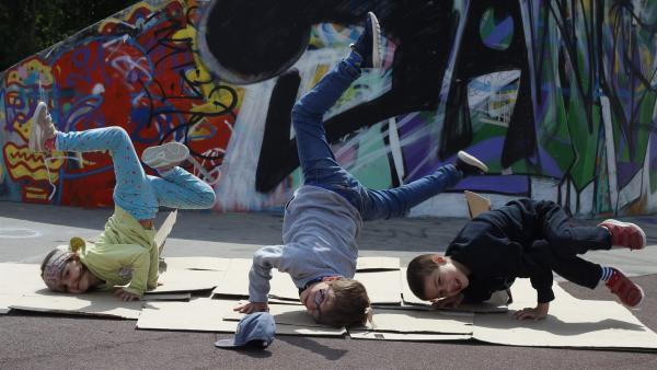 Max (Mi.) tanzt mit Benicio (re.) und Maya (li.) im Park Breakdance. Ihre Moves sind so cool, das bald erste Passanten begeistert stehen bleiben und zuschauen. | Rechte: ZDF/Studio.TV.Film GmbH