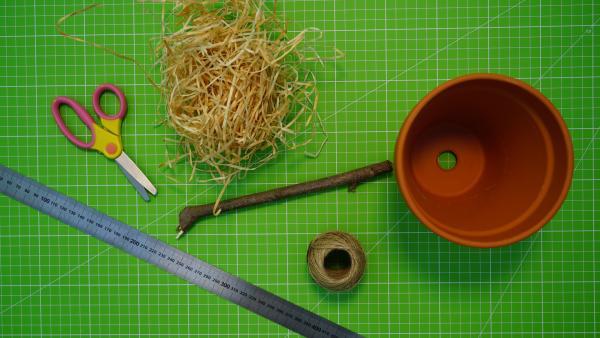Materialien: ein Blumentopf ( etwa 10-13 cm Durchmesser), Holzwolle oder Heu, robuste Schnur (etwa 50 cm), ein kleines Stück Zweig und eine Schere. | Rechte: kika