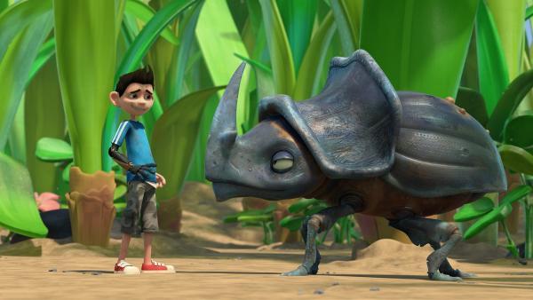 Wia sitzt in Zaks Ohr und unterhält sich mit ihm. Das irritiert den Nashornkäfer.    Rechte: KiKA/One Animation PTE LTD.
