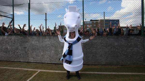 Boggy  (Jonnie Kimmins) als Maskottchen feuert die Mannschaft an. | Rechte: WDR/Short Form (JJI) Ltd