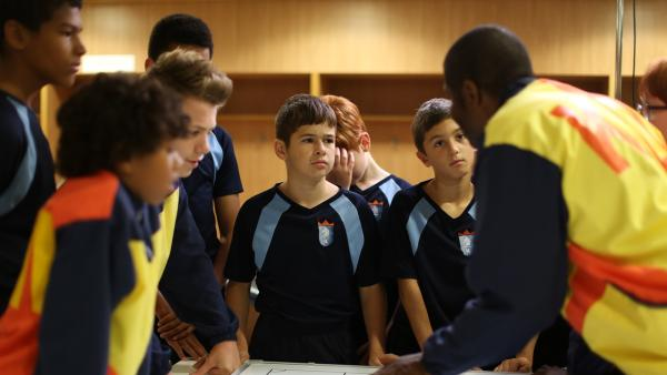 Trainer Hansard (Brian Bovell, rechts) erklärt Jamie (Louis Dunn, Mitte) und dem Team seine Strategie. | Rechte: WDR/Short Form (JJI) Ltd
