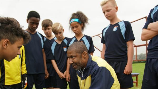 Trainer Hansard (Brian Bovell) schwört Jack (Lenna Gunnning-Williams) und das Team auf den Sieg ein. | Rechte: WDR/Short Form (JJI) Ltd