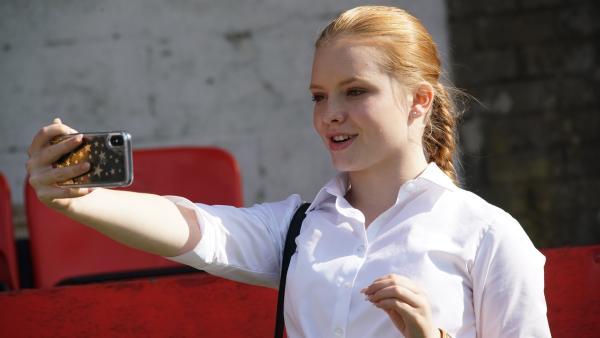 Sienna (Ellie Botterill) kümmert sich um den Social Media-Auftritt von Phoenix.   Rechte: WDR/Short Form (JJI) Ltd
