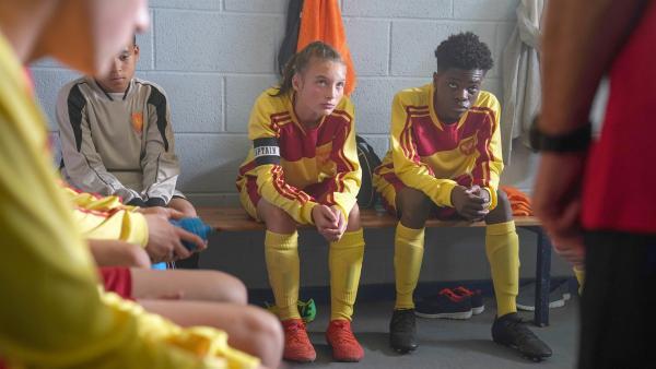 Als Mannschaftskapitänin schwört Alba (Elena Cole) Eric (Morgan Hudson) und die anderen auf das Spiel ein. | Rechte: WDR/Short Form (JJI) Ltd