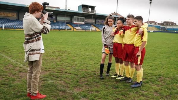 Boggie (Jonnie Kimmins) schießt ein Bild der Phoenix FC-Legenden Ruby (Zoe Hall), Jack (Lenna Gunning Williams), Dillon (Patrick Ward) und Jamie (Louis Dunn).   Rechte: WDR/Short Form (JJI) Ltd