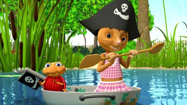 Lu und Naya paddeln in einer großen Pfütze. Naya trägt eine Piratenkappe und die Schüssel, die ihnen als Boot dient, ist mit einer Piratenflagge geschmückt. | Rechte: ZDF