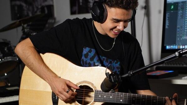 Komponist Levent trägt Kopfhörer und spielt Gitarre | Rechte: privat/KiKA