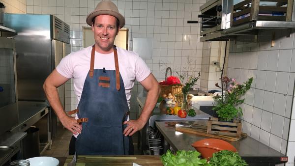 Ben steht in seiner Küche mit Kochschürze, bereit zum Kochen. | Rechte: KiKA/ Elisabeth Möckel