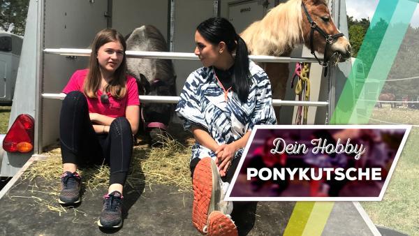 Emilie sitzt mit Jess auf der Rampe eines Pferdehängers. Ein Pony schaut im Hintergrund. | Rechte: KiKA / Andrea Thoben