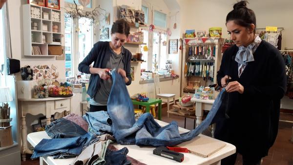Jess und Anne trennen ein paar alte Jeans auf, um daraus etwas neues, praktisches entstehen zu lassen. | Rechte: KiKA/Grit Häfer