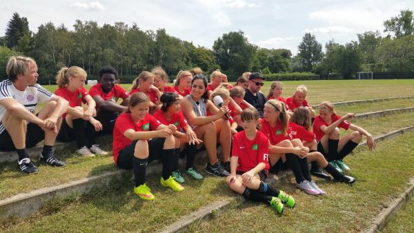 Ben und Jess entspannen mit den Mädels und ihrem Trainer am Spielrand und quatschen dabei über die Zeit im Camp. | Rechte: KiKA/Tina Wilß