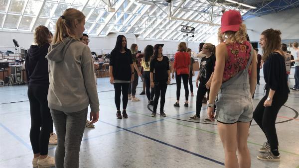 Die Schüler der Regelschule Hermsdorf lernen gerade mit einer Studentin der Young Americans ihren Teil des Auftrittes. | Rechte: KiKA/Sabine Krätzschmar