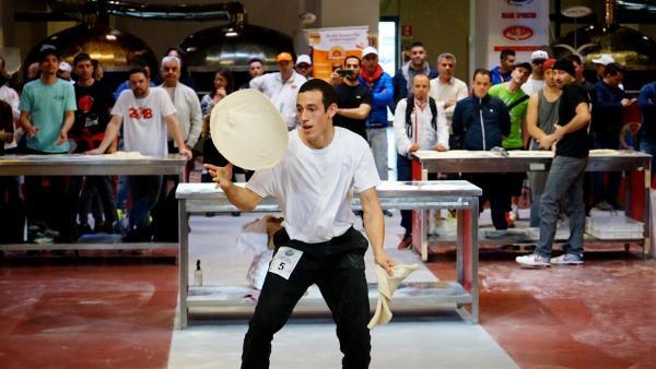 Bei der Pizza-Weltmeisterschaft in Parma fliegen die Teigscheiben nur so durch die Lüfte. | Rechte: KiKA/Franziska Gruber