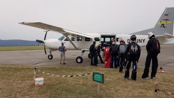 Leo und Jess steigen mit den anderen Fallschirmspringern ins Flugzeug, aus dem sie dann springen werden. | Rechte: KiKA/Lisa Dimmerling