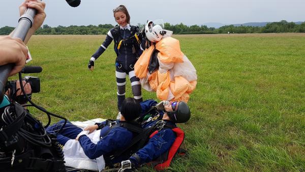 Leo begrüßt die beiden Fallschirmspringer. | Rechte: KiKA/Lisa Dimmerling